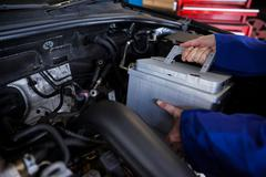 Mechanic removing car battery from car Stock Photos