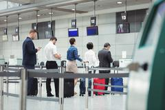 Passengers waiting in queue at a check-in counter with luggage Stock Photos