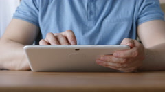 A hands of young man with a tablet PC at the table at home Stock Footage