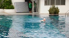 Closeup man swims free style with cleaning staff Stock Footage