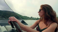 Summer vacation - young girl driving a motor boat Stock Footage