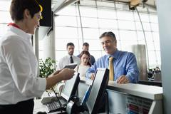 Airline check-in attendant handing boarding pass to passenger Stock Photos