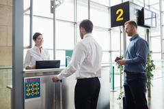 Man giving his passport to airline check-in attendant Stock Photos