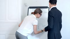 Businesswoman shows business plan to her partner at office Stock Footage