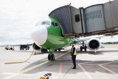 Airport ground crew worker standing next to airplane Stock Photos