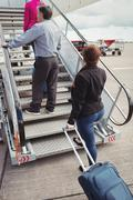 Passengers climbing on the stairs and entering into the airplane Stock Photos