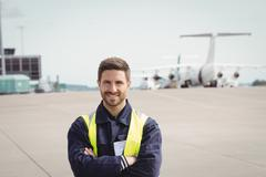 Portrait of airport ground crew standing with arms crossed Stock Photos