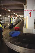 Airport ground crew unloading luggage from baggage carousel Stock Photos