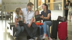 Family waiting for your flight or train and use the tablet and phones while Stock Footage