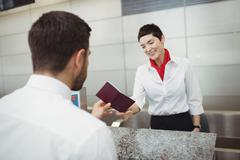 Airline check-in attendant handing passport to passenger Stock Photos