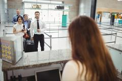 Passengers waiting in queue at check-in counter Stock Photos