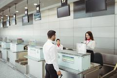 Airline check-in attendant checking passport of passenger Stock Photos