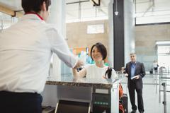 Airline check-in attendant handing passport to passenger Stock Photos