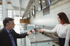 Businessman showing mobile boarding pass to airline check-in attendant Stock Photos
