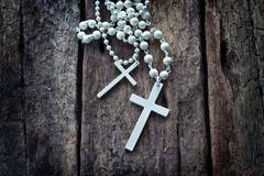White necklace crucifix on old wooden table Stock Photos