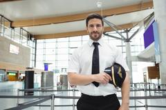 Pilot standing in airport terminal Kuvituskuvat
