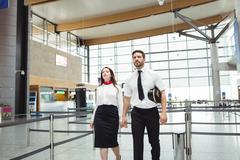 Pilot and flight attendant walking in the airport terminal Kuvituskuvat