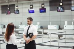 Pilot and flight attendant interacting with each other Stock Photos