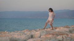 A beautiful young woman in the dress walking on the rocks Stock Footage