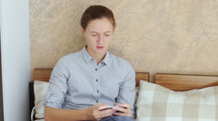 Girl using her smartphone while sitting down in bed Stock Footage