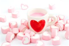 Red heart symbol on strawberry milk cup and pink candy heart on white background Stock Photos