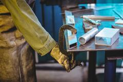 Mid-section of female welder using clamp tool Stock Photos