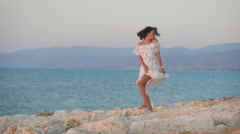 A beautiful young woman in the dress dancing on the rocks Stock Footage