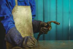 Mid-section of female welder holding welding torch Stock Photos