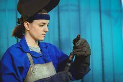 Female welder examining a welding torch Stock Photos