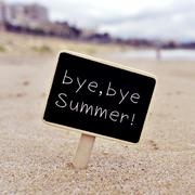 Text bye, bye summer in a signboard on the beach Stock Photos