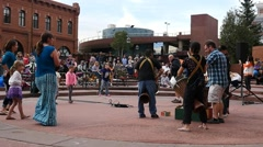 People dance to a drum corps in a town square Stock Footage