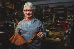 Portrait of shoemaker holding a boot and piece of material Stock Photos