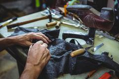 Shoemaker cutting a piece of material Stock Photos
