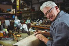 Portrait of shoemaker cutting a piece of material Stock Photos