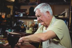 Shoemaker cutting a piece of leather Stock Photos