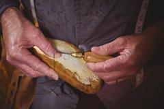 Shoemaker stitching shoe sole with needle Stock Photos
