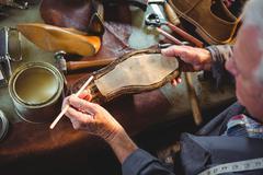 Shoemaker applying glue on shoe sole Stock Photos