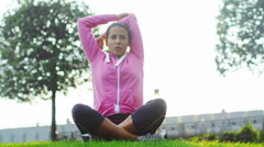 4K Woman doing stretches to prepare for workout in the park Stock Footage