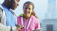 4K Personal trainer with tablet working with female client outdoors in the city Stock Footage