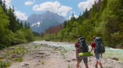 Tracking Two Men Hiking along a Beautiful River Stock Footage