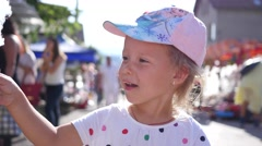 Cute little kid girl face portrait eating a blue cotton candy Stock Footage