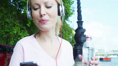 4K Female runner in the city with headphones and mobile phone takes a break Stock Footage