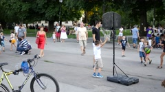 Children play basketball on a street sport festival in city center park Stock Footage