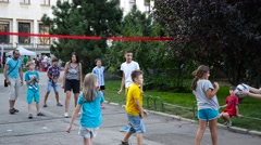 Children play volleyball on a street sport festival in city center park Stock Footage