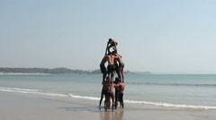 Happy man making human pyramid on the Palolem beach Stock Footage
