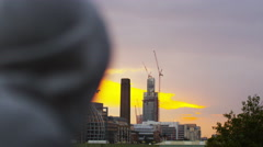 4K Athletic hooded man looks out over view of the city at sunset Stock Footage