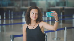Passenger, woman in the airport, waiting for her flight making selfie with he Stock Footage