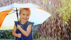 Carefree girl three years under the umbrella of color. Hiding from the rain Stock Footage