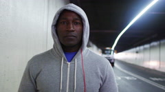 4K Portrait of athletic black male in a hooded sweatshirt, in urban environment Stock Footage