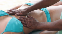 Close up of therapist's hands doing tummy massage on woman. Stock Footage